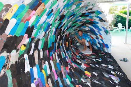 PHOTO: David Day inside the life-size wave he made from thongs. (ABC Tropical North: Sophie Kesteven )